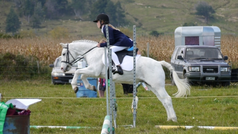 Lauren and her old pony Aztec jumping at their Pony Club Show